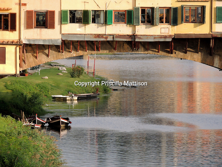 Florence, Italy - October 3, 2012:  Boats float under the Ponte Vecchio.