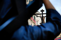 The Holy Week participant (Nazareno) carries a wooden cross in the procession during the Easter celebration in Malaga, Spain, 7 April 2007.