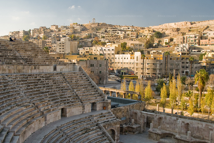 The Roman theater frames a view of central Amman, Jordan, rising to the Citadel and remains of the Roman Temple of Hercules on the hill beyond.  Columns and trees just outside the theater mark the site of what was once the one of the largest fora in the Roman Empire.  Like Rome itself, Amman is built on seven hills.  This was a prominent provincial capital named Philadelphia under the rule of Ancient Rome.  © Rick Collier