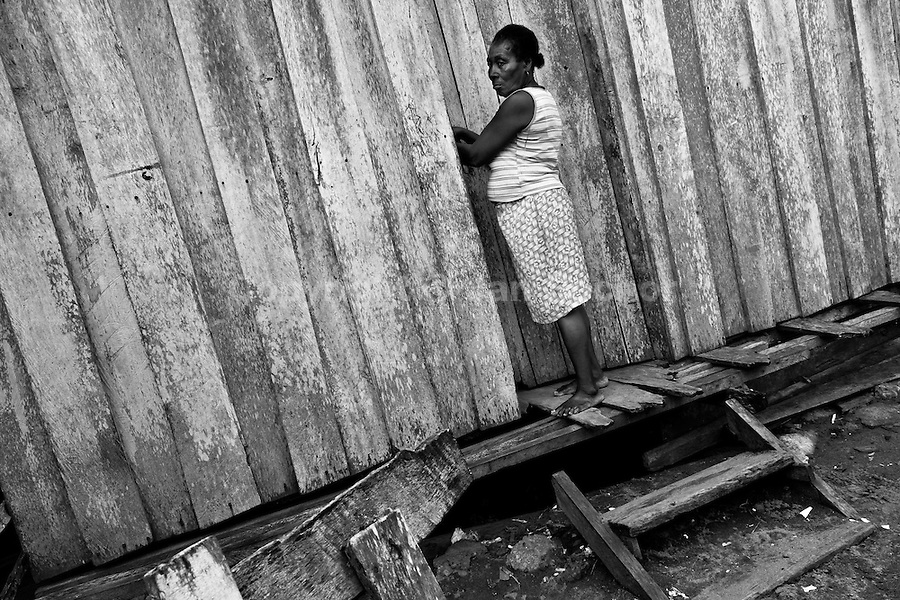 A displaced woman, working as a mussel picker in the mangroves, enters her wooden house in the stilt village close to Tumaco, Nariño dept., Colombia, 15 June 2010. With nearly fifty years of armed conflict, Colombia has the highest number of civil war refugees in the world. During the last ten years of the civil war more than 3 million people have been forced to abandon their lands and to leave their homes due to the violence. Internally displaced people (IDPs) come from remote rural areas, where most of the clashes between leftist guerrillas FARC-ELN, right-wing paramilitary groups and government forces takes place. Displaced persons flee in a hurry, carrying just personal belongings, and thus they inevitably end up in large slums of the big cities, with no hope for the future.