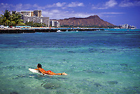 Girl paddling surfboard in red suit in clear blue water with Waikiki and Diamond Head in background