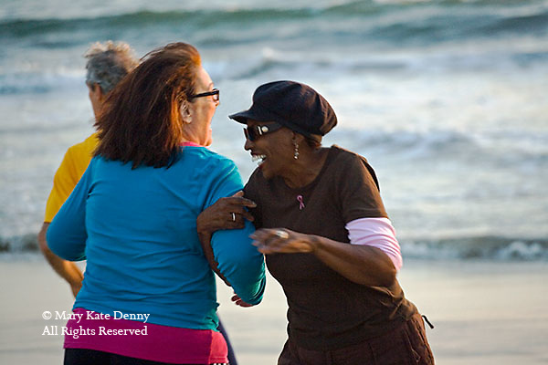 One white senior woman and one black senior woman link arms together dancing and exercising on Playa del Rey Beach in California