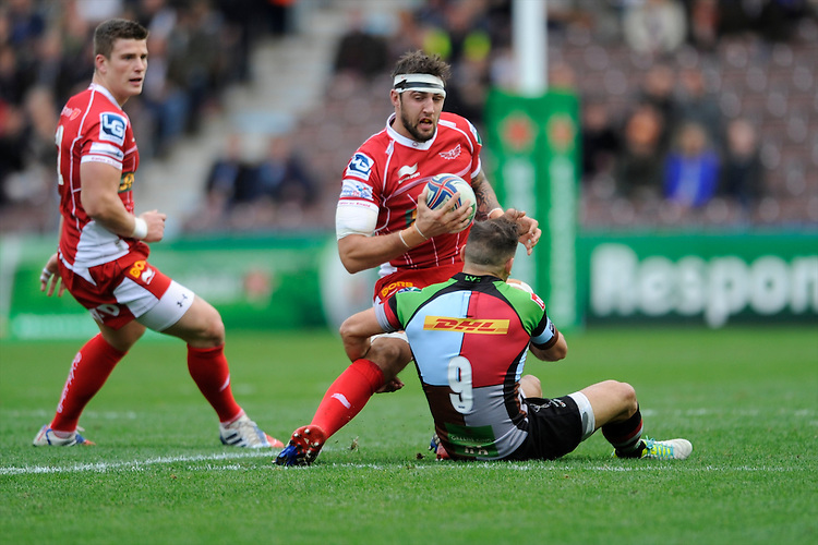 Josh Turnbull of Scarlets is tackled by Danny Care of Harlequins during the Heineken Cup Round 1 match between Harlequins and Scarlets at the Twickenham Stoop on Saturday 12th October 2013 (Photo by Rob Munro)