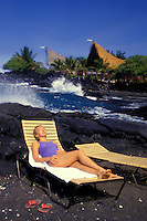 Woman lounging in sun near the ocean on vacation at Kona village resort on the Big island