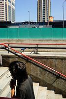 """Milano, quartiere Garibaldi, progetto di riqualificazione dell'area di Porta Nuova. Un uomo con una sigaretta sale la scalinata della metropolitana con la stazione e le Torri sullo sfondo --- Milan, Garibaldi district,  requalification project of """"Porta Nuova"""" area. A man with a sigarette climbing the stairs of the subway with the station and the Towers on the background"""