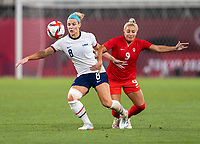 KASHIMA, JAPAN - AUGUST 2: Julie Ertz #8 of the USWNT fights for the ball with Adriana Leon #9 of Canada during a game between Canada and USWNT at Kashima Soccer Stadium on August 2, 2021 in Kashima, Japan.