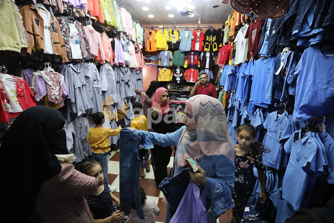 Palestinians shop during preparation for the new school year at a market in Nuseirat refugee camp in the center of the Gaza Strip, on  11 August 2021. The fiscal position in Gaza strip has worsened not only due to the outbreak but also due to a political standoff that is disrupting the flow of revenues. The outlook remains precarious and subject to numerous political, security and health risks. Photo by Ashraf Amra