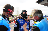 Mar. 10, 2012; Gainesville, FL, USA; NHRA top fuel dragster driver T.J. Zizzo is helped with safety gear by crew members during qualifying for the Gatornationals at Auto Plus Raceway at Gainesville. Mandatory Credit: Mark J. Rebilas-