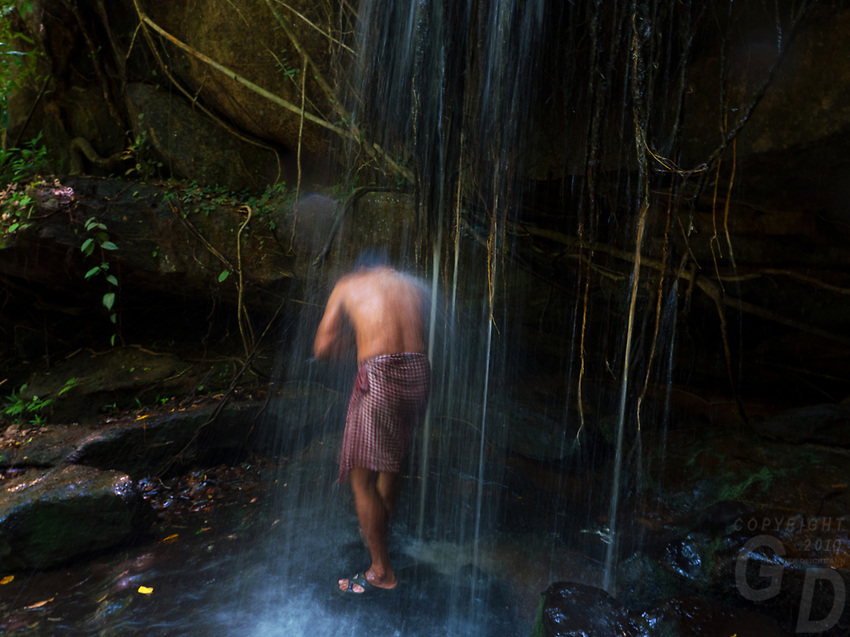 """Local Khmer man washing and cleaning himself under the waterfall at Kbal Spean (""""Bridge Head"""") is an Angkorian era archaeological site on the southwest slopes of the Kulen Hills to the northeast of Angkor in Siem Reap District, Siem Reap Province, Cambodia. It is situated along a 150m stretch of the Stung Kbal Spean River, 25 kilometres (16mi) from the main Angkor group of monuments, which lie downstream.<br /> The site consists of a series of stone rock relief carvings in sandstone formations of the river bed and banks. It is commonly known as the """"Valley of a 1000 Lingas"""" or """"The River of a Thousand Lingas"""". 11th and 12th centuries.<br /> The motifs for stone carvings are mainly myriads of lingams (phallic symbol of Hindu god Shiva), depicted as neatly arranged bumps that cover the surface of a sandstone bed rock, and lingam-yoni designs. There are also various Hindu mythological motifs, including depictions of the gods Shiva, Vishnu, Brahma, Lakshmi, Rama, and Hanuman, as well as animals (cows and frogs)."""