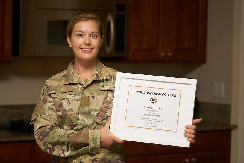 US military soldier in uniform in her kitchen with diploma. For sale as stock photography, DOD complient.