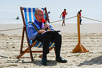 BNPS.co.uk (01202 558833)<br /> Pic: Graham Hunt/BNPS<br /> <br /> Town mayor Cllr Colin Huckle chairs the meeting.<br /> <br /> Town hall officials swapped their stuffy chambers for the sand and sea today as they took part in what is thought to be the UK's first ever council meeting on a beach.<br /> <br /> Weymouth Town Council in Dorset held the event on the beach in protest at the Government banning virtual meetings.<br /> <br /> Since May 6, votes cast at virtual council meetings have not been legally binding following a controversial ruling upheld by a High Court judge.<br /> <br /> But because social distancing is difficult to practice in many town halls, officials in Weymouth used a loophole in the rules to meet on a beach.
