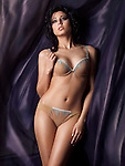 Young glamorous woman wearing beautiful beige lingerie standing surrounded by dark flowy fabric Image © MaximImages, License at https://www.maximimages.com