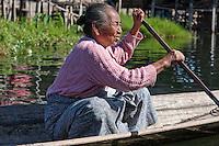 Myanmar, Burma.  Old Intha Woman Rowing her Boat, Inle Lake, Shan State.