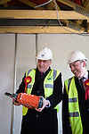 © Joel Goodman - 07973 332324 .  04/02/2014 . Manchester , UK . Ed Balls with a nail gun and Mike Kane . Ed Balls , MP for Morley and Outwood and Shadow Chancellor of the Exchequer the Labour Party , joins Labour candidate Mike Kane on the campaign trail ahead of the Wythenshawe and Sale East by-election , following the death of MP Paul Goggins . They visit apprentices at the Leybrook Road building site in Wythenshawe where apprentice builders work on bungalows built for affordable rent . Photo credit : Joel Goodman