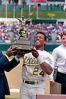 OAKLAND, CA - Rickey Henderson of the Oakland Athletics smiles and lifts up a trophy after setting the all time career stolen base record by stealing base #939 during a game against the New York Yankees at the Oakland Coliseum in Oakland, California on May 1, 1991. Photo by Brad Mangin