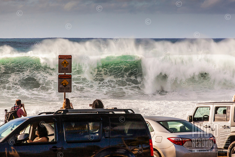 Spectators watch giant waves during a large winter swell at Shark's Cove off of Kamehameha Hwy., North Shore, O'ahu.