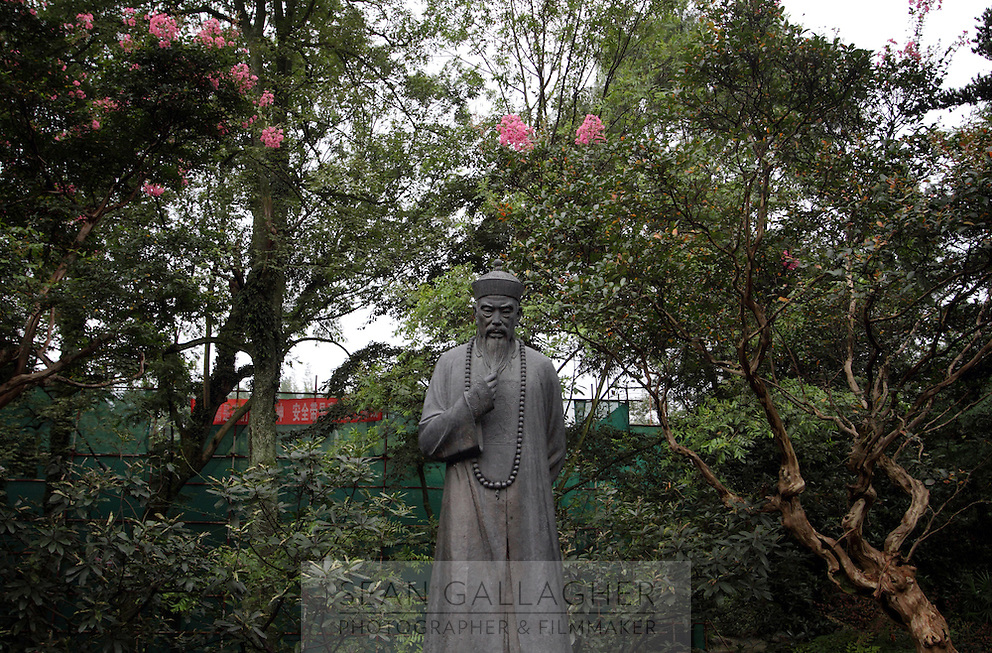 """A statue of a Taoist figure stands within the grounds of the Dujiangyan Irrigation System. The system is regarded as an """"ancient Chinese engineering marvel."""" By naturally channeling water from the Min River during times of flood, the irrigation system served to protect the local area from flooding and provide water to the Chengdu basin. Sichuan Province. 2010"""