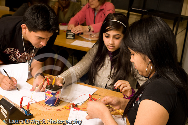 Education High School physics lab on electrical circuits one male and two female lab partners working together horizontal