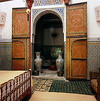 Elaborately decorative double doors lead from the bedroom suite to a sitting area beyond. Intricately patterned tiling and textured rugs add to the overall style of the room.