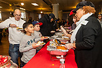 WATERBURY, CT. 21 December 2019-122119BS301 - The Martinez family, Dad Eddie, and his two sons Ely, 8, and Edgardo, 6, wait in line to get a hot meal, during a Christmas Party for the less fortunate and homeless at the Basilica of Immaculate Conception in Waterbury on Saturday. Bill Shettle Republican-American