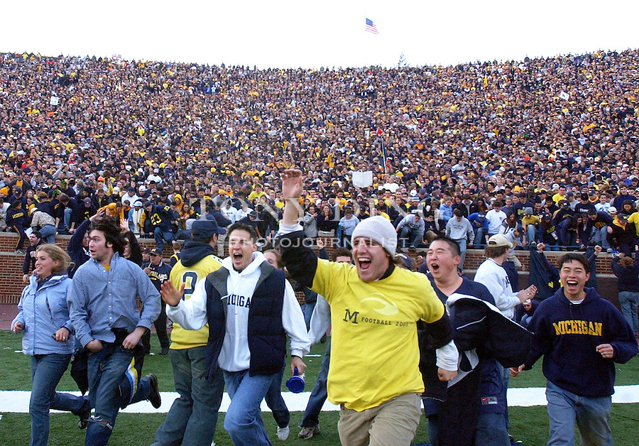 Michigan student fans rush the field after the Wolverine's 35-21 upset of Ohio State on Saturday, November 22, 2003 in Ann Arbor, Mich. This was the 100th rivary match between UM and OSU. (TONY DING/The Michigan Daily)