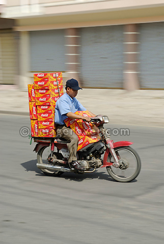 Asia, Vietnam, Nha Trang. Transportation of Coca Cola cans by motorbike.