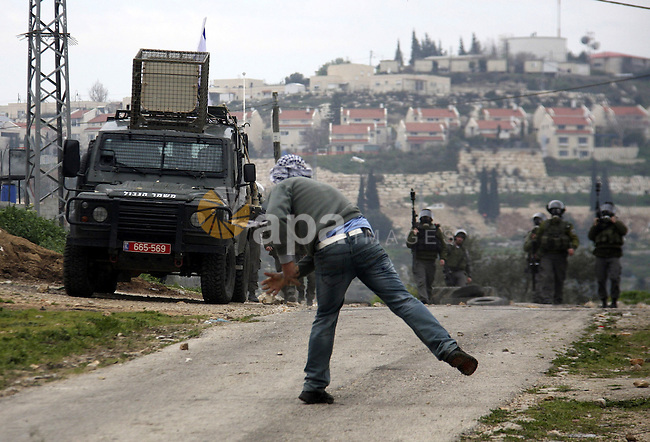 A Palestinian protester throws stones at Israeli soldiers during a demonstration against the expropriation of Palestinian land by Israel in the village of Kfar Qaddum, near the West Bank city of Nablus, on February 24, 2012.  Photo by Wagdi Eshtayah