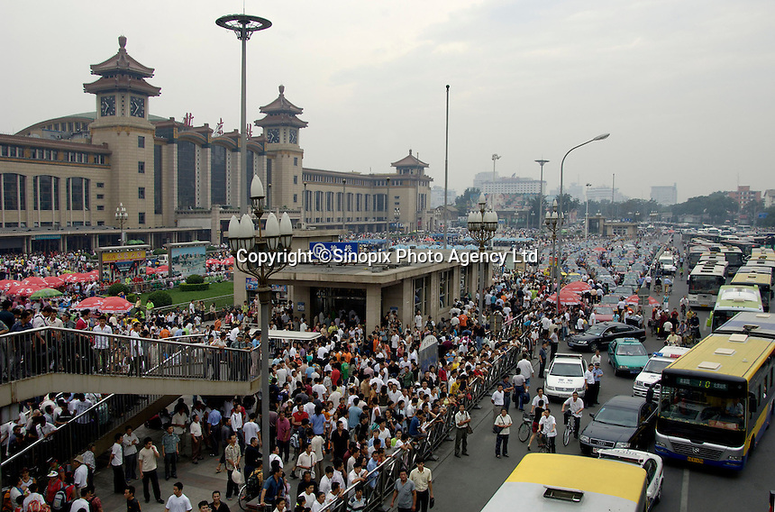 Traffic is disrupted due to a migrant worker who threatens to jump from the top of an overpass bridge while demanding the government help him get his unpaid salaries in front of Beijing raiway station. Payment default on migrant workers is common in recent years, many migrant workers have been forced to resort to desperate measures to receive what is owed to them..22 Aug 2006