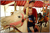Three boys and a woman ride the merry-go-round at an amusement park.  Model released image can be used to illustrate many purposes.