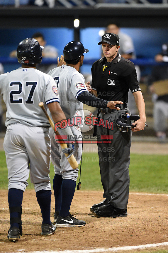Staten Island Yankees coach Luis Figueroa (2) stands in between Isaias Tejeda (27) and umpire Justin Houser after Tejeda was ejected from the game during a game against the Batavia Muckdogs on August 7, 2014 at Dwyer Stadium in Batavia, New York.  Staten Island defeated Batavia 2-1.  (Mike Janes/Four Seam Images)