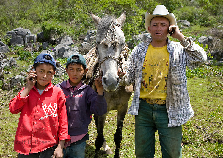 Father and sons posing with cell phones in the countryside near San Nicolas, Western Highlands, Guatemala
