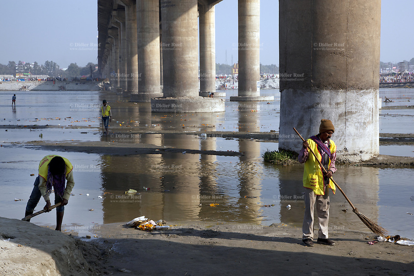 "India. Uttar Pradesh state. Allahabad. Maha Kumbh Mela. Three men, all street cleaners, are collecting plastic and garbages floating on the Ganges' river on the day of Royal bath on Mauni Amavasya Snan (Dark moon). The ritual ""Royal Bath"" is timed to match an auspicious planetary alignment, when believers say spiritual energy flows to earth. The Kumbh Mela, believed to be the largest religious gathering is held every 12 years on the banks of the 'Sangam'- the confluence of the holy rivers Ganga, Yamuna and the mythical Saraswati. The belief is that bathing and taking a holy dip will wash and free one from all the past sins, get salvation and paves the way for Moksha (meaning liberation from the cycle of Life, Death and Rebirth). The Maha (great) Kumbh Mela, which comes after 12 Purna Kumbh Mela, or 144 years, is always held at Allahabad. Uttar Pradesh (abbreviated U.P.) is a state located in northern India. 10.02.13 © 2013 Didier Ruef"