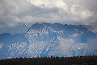 Float plane flies by Mount Katolinat, while transporting tourists to Katmai National Park, Alaska.