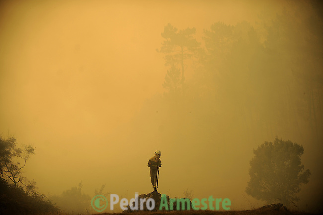Members of the fire Galician brigade are seen around the area where a fire burns in Porqueira, near A Coruña, on august 14, 2010. (c)Pedro ARMESTRE