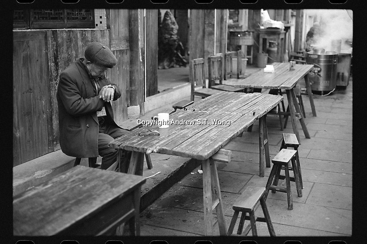 Youbu Township, Lanxi City, Zhejiang Province - An elderly man checks his watch outside an old tea house early in the morning, December 2020., The ancient township of Youbu is located along the Qiantang River.