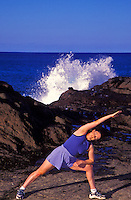 Woman doing yoga near Halona blow hole, Oahu