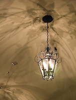 A fine art abstract of a hanging glass lantern, with 4 candle bulbs, reflecting lovely shadows of leaves and arcing lines, in sepia tones, on the ceiling above.
