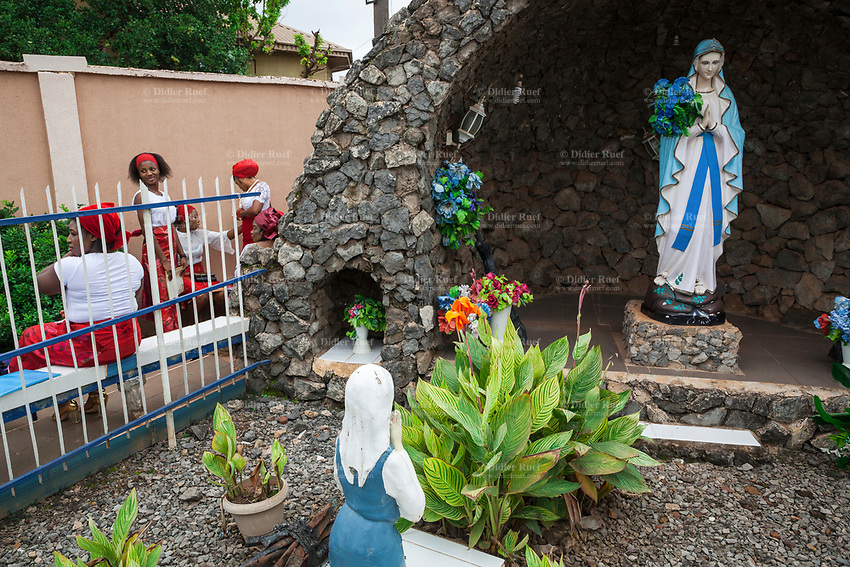 """Nigeria. Enugu State. Enugu. St. Theresa's Parish. Catholic Church. A plaster statue of the Virgin Mary standing in """"Our Lady of Lourdes, Grotto"""" while another sculpture is a woman praying on her knees. Mary was a first-century BC Galilean Jewish woman and the mother of Jesus according to the New Testament. On the other side of the fence, a group of Igbo women dressed with red and white clothes. They belong to a choir rehearsing before the Sunday morning mass. All women wear a head tie which is a women's cloth head scarf. The head tie is used as an ornamental head covering or fashion accessory, or for functionality in different settings. Its use or meaning can vary depending on the country and/or religion of those who wear it. The head tie is called gele in Nigeria. Enugu is the capital of Enugu State, located in southeastern Nigeria. 30.06.19 © 2019 Didier Ruef"""