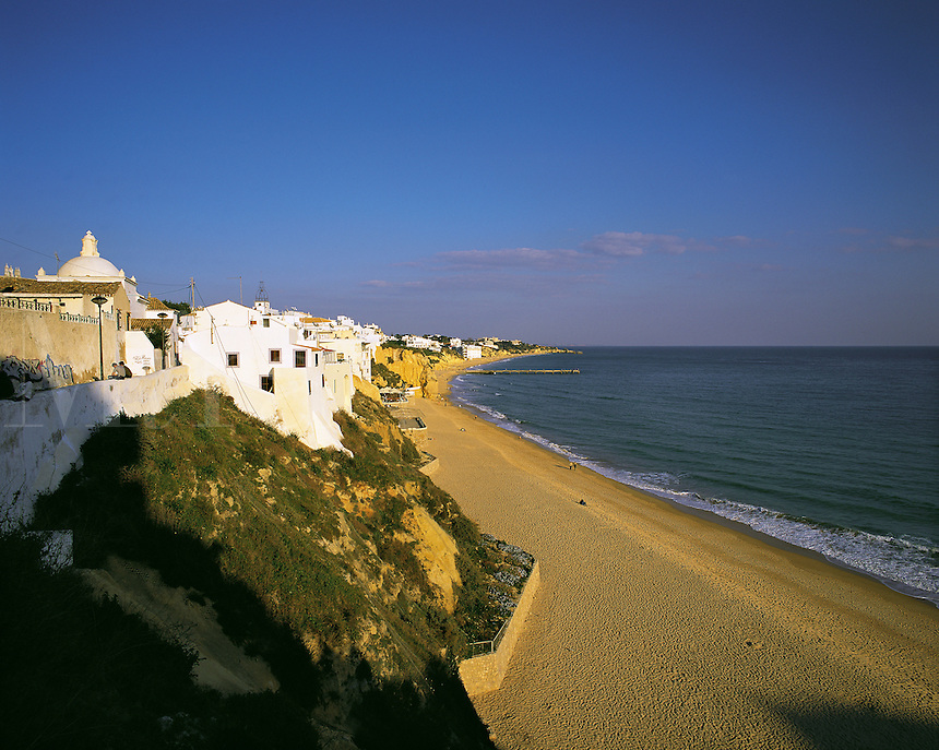 Early morning, looking east along the nearly deserted main beach at Albufeira, Algarve, Portuga