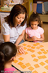 Preschool ages 3-5 female teacher sitting with two girls playing card memory game vertical