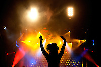 A stage performer is silhouetted against colorful theater lights during First Night Charlotte 2010. The family-friendly public event (no alcohol allowed) is an annual cultural New Year's Eve celebration held in downtown / uptown / Charlotte center city. Charlotte First Night - An Imagination Celebration brought together artists, musicians, dancers and more from across the country. The New Year's event is organized by Charlotte Center City Partners, which facilitates and promotes the economic and cultural development of this North Carolina urban core.