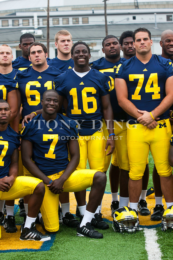 Michigan quarterback Devin Gardner, bottom center, and quarterback Denard Robinson (16) pose for a group photo with teammates at the annual NCAA college football media day, Sunday, Aug. 22, 2010, in Ann Arbor, Mich. (AP Photo/Tony Ding)