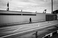 Switzerland. Canton Geneva. Geneva Airport. A lonely man walks on the sidewalk. After grounding its fleet of planes, two aircrafts from SWISS International Airlines are parked in the airport after the lockdown due to the coronavirus (also called Covid-19). Owing to the global health crisis, the European and International air travel is stopped in a standstill. Geneva Airport (French: Aéroport de Genève,(IATA: GVA, ICAO: LSGG)), formerly and still unofficially known as Cointrin Airport, is the international airport of Geneva. The flag of Switzerland displays a white cross in the centre of a square red field. The white cross is known as the Swiss cross. 5.05.2020 © 2020 Didier Ruef