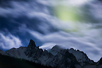 Aurora borealis behind moonlit clouds, mount Snowden, Brooks Range, Arctic, Alaska
