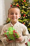 Boy (6-7) holding Christmas present