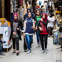 Fes, Morocco.  Young Moroccan Women Walking in  the Medina, Tala'a Seghira Street, Fes El-Bali.  Modern Dress Styles.