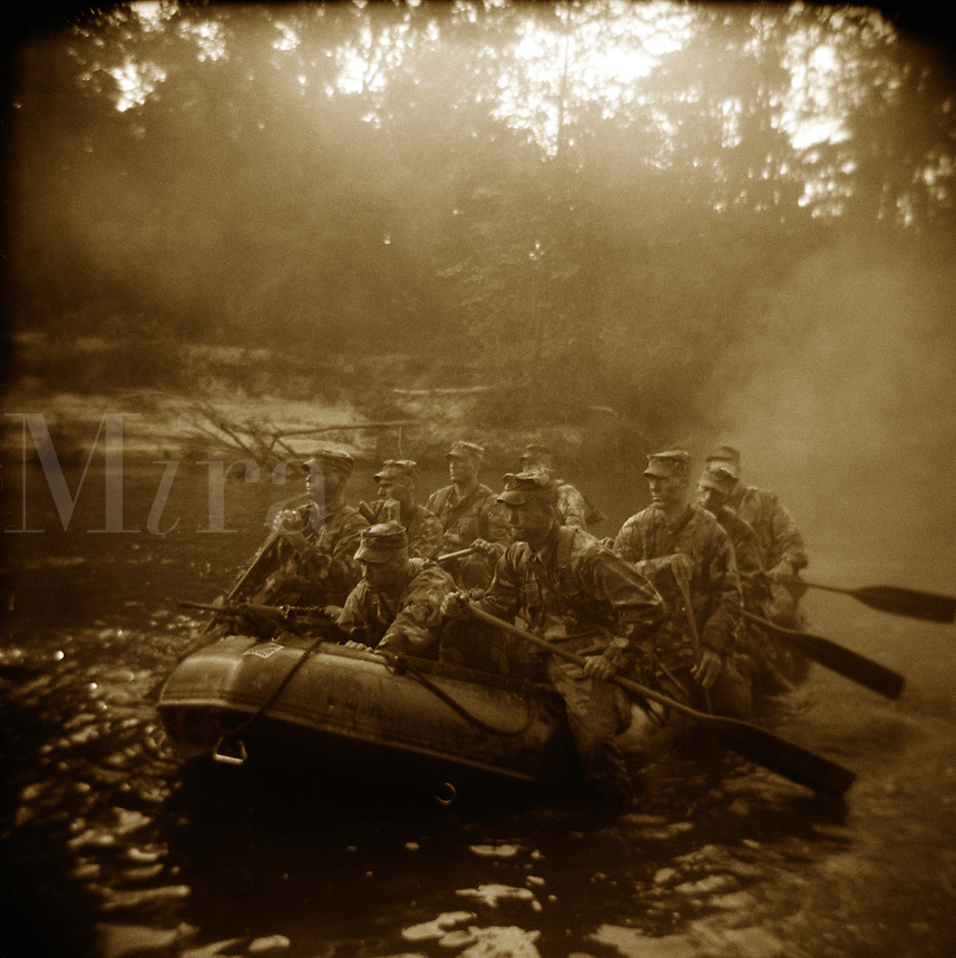 A squad of US Army Rangers during early morning practice of small boat maneuvers in an inflatable rubber boat, Uchee Creek, Ft. Benning, Georgia.