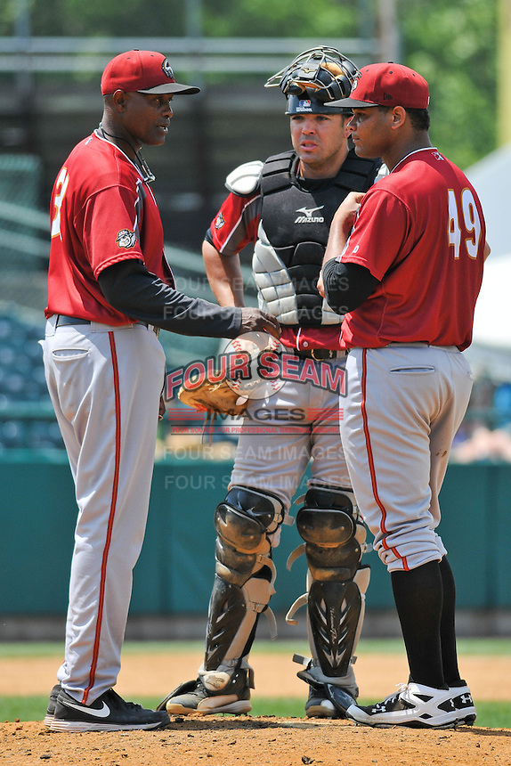 Pitching Coach Stan Kyles (38), Catcher Ralph Henriquez (3) and Joan Montero (49) meet on the mound during a game against the New Britain Rock Cats at New Britain Stadium on June 25, 2014 in New Britain, Connecticut.  New Britain defeated Altoona 3-1.  (Gregory Vasil/Four Seam Images)