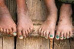 Children's feet sitting on a ladder, Paro Valley, Bhutan