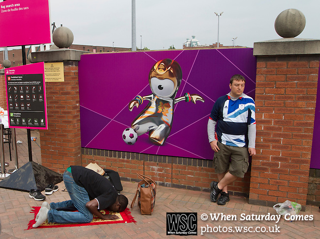 Uruguay 2 United Arab Emirates 1, Great Britain 1 Senegal 1, 26/07/2012. Old Trafford, Olympic Games. A Senegalese man praying outside Manchester United's Old Trafford stadium prior to the Men's Olympic Football tournament matches at the venue. The double header of matches resulted in Uruguay defeating the United Arab Emirates by 2-1 while Great Britain and Senegal drew 1-1. Over 72,000 spectators attended the two Group A matches. Photo by Colin McPherson.